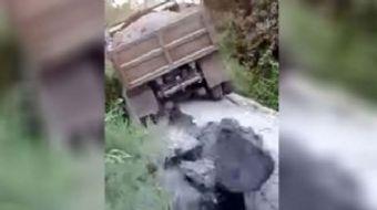 Tahta köprü kum yüklü kamyonun ağırlığına dayanamadı. Köprü bir anda çökerken, kamyon da aşağı yuvar
