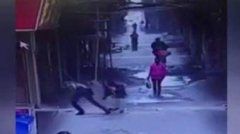 Çin'de kaydedilen görüntülerde, sokak ortasında güpegündüz genç bir kızın arkasından yaklaşan adam,